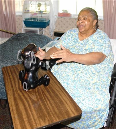 In the picture, a resident at the NHC Healthcare assisted-living facility in Maryland Heights, Missouri, plays with AIBO, a robotic dog. Researchers found that the robot dog was about as good as a real dog at easing the loneliness of nursing home residents in a study. The woman in the photo is Gladys Moore. She is playing with AIBO, though she was not officially part of the study. REUTERS/Saint Louis University/Handout