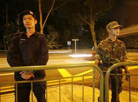 A police officer (L) and a solider stand guard on a main road in Singapore February 27, 2008. The accused leader of the Singapore wing of the Islamic militant network Jemaah Islamiah (JI), Mas Selamat bin Kastari, escaped on Wednesday from a detention centre on the island, the government said. REUTERS/Vivek Prakash
