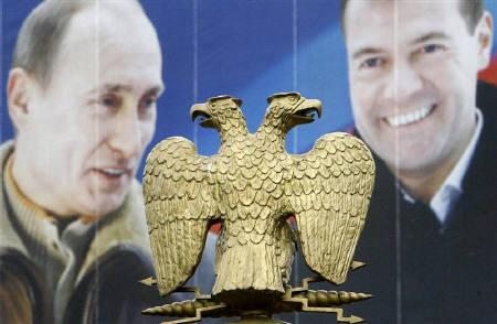 A Russian two-headed eagle is seen against an election poster depicting Russia's President Vladimir Putin (L) and First Deputy Prime Minister and presidential candidate Dmitry Medvedev in central Moscow February 28, 2008. REUTERS/Denis Sinyakov