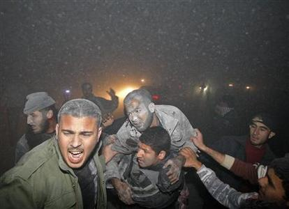 Palestinians evacuate a wounded man after an Israeli missile destroyed the Workers Union headquarters in Gaza February 28, 2008. REUTERS/Mohammed Salem