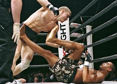 Andrei Semenov of Russia (L) fights with Jorge Santiago of the U.S. during a BoDog Fight mixed martial arts event in St Petersburg April 14, 2007. CBS is bringing mixed martial arts, the bone-crunching combat sport popularly known as ''cage fighting,'' to prime-time television this spring, the U.S. network said on Thursday. REUTERS/ITAR-TASS/PRESIDENTIAL PRESS SERVICE