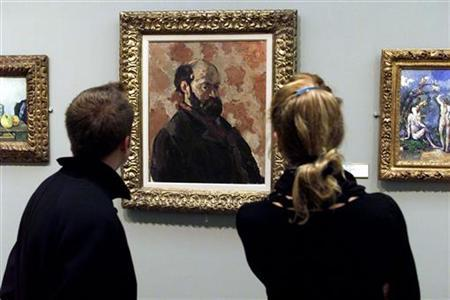 Visitors at the Musee d'Orsay admire a self-portrait by French painter Paul Cezanne, ''Portrait de l'artiste au fond rose'' one the masterpieces donated to museums in France, October 16, 2000. REUTERS/John Schults