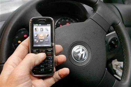 A mobile phone is used in a car in this posed photograph in central London February 27, 2007. A motorist who ploughed into a cyclist while sending a text from her mobile phone was jailed for four years on Friday. REUTERS/Toby Melville