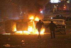 <p>Сторонники армянской оппозиции на фоне горящей полицейской машины в Ереване 2 марта 2008 года. Восемь человек погибли и 33 полицейских получили ранения в ходе ночных столкновений сторонников армянской оппозиции с силами правопорядка, сообщила полиция. (REUTERS/David Mdzinarishvili)</p>