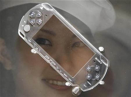 A model is reflected on Sony's PlayStation portable (PSP-2000 model) at the Tokyo Game Show in Chiba, east of Tokyo September 20, 2007. Sony said it would add a Skype Web phone function to its PlayStation Portable later this month in Japan in a bid to boost the appeal of the handheld machine, which is running behind Nintendo Co Ltd's DS in sales. REUTERS/Issei Kato