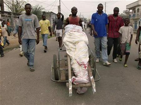 Demonstrators push the body of a person, apparently killed during deadly protests, in the port city of Douala February 27, 2008. REUTERS/Talla Ruben