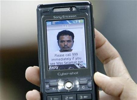 A member of the media displays an MMS message, showing the portrait of Mas Selamat bin Kastari, for the camera in Singapore March 2, 2008. Singapore's state-controlled media and government have come under fire from critics and Internet bloggers for failing to give the public important answers on the escape of Kastari. REUTERS/Vivek Prakash