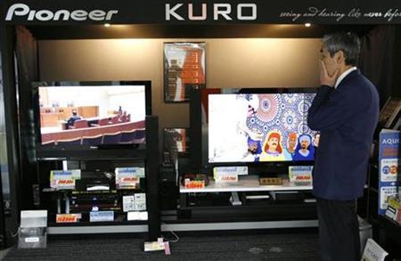 An employee reacts in front of Pioneer Corp's plasma televisions at an electric home appliances shop in Tokyo March 4, 2008. Japan's Pioneer Corp is finalizing plans to stop all production of plasma display panels in a bid to turn around its loss-making flat TV operations, an industry source briefed on the plan said on Tuesday. REUTERS/Toru Hanai