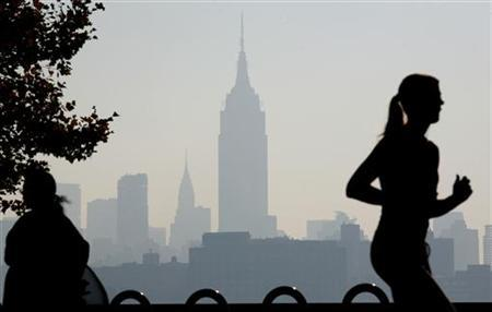 The haze shrouded skyline of New York is a backdrop to a jogger running along the Hudson River in Hoboken, New Jersey August 3, 2006. . REUTERS/Gary Hershorn