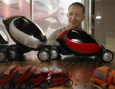 Franco Vairani, a PhD student in the Department of Architecture at the Massachusetts Institute of Technology, looks over models of the City Car, a collapsible, electric, battery powered car he designed for his thesis at MIT, in Cambridge, Massachusetts November 13, 2007. REUTERS/Brian Snyder
