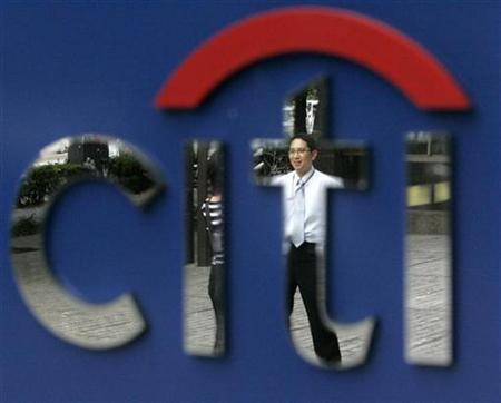 A man is reflected in the Citibank logo in Tokyo November 5, 2007. Citigroup forecast $9 billion of writedowns at U.S. investment banks in the first quarter of 2008, primarily driven by additional leveraged loan and mortgage-related losses. REUTERS/Toru Hanai