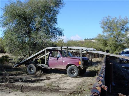 A modified pickup truck with extendable ramps stands idle a few yards to the south of the fence marking the U.S. and Mexico border near Campo, California in this undated file photo provided by the U.S. Border Patrol. Once extended, the ramps were used by Mexican drug traffickers to drive vehicles packed with bales of marijuana into the United States. Mexican drug and human smugglers are constantly adapting new techniques to try and defeat increased security on the nearly 2,000-mile (3,200-km) international boundary. REUTERS/U.S. Border Patrol/Handout