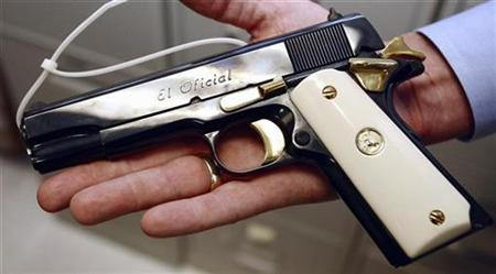 Senior Special Agent in charge William Newell holds a Colt. 38 Super semi-automatic pistol that was confiscated and is being stored in one of the ''vaults'' at the local office of the ATF (Bureau of Alcohol, Tobacco and Firearms) as evidence for trial or waiting to be melted down in Phoenix, Arizona, July 6, 2007. REUTERS/Jeff Topping