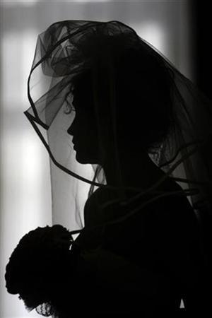 A woman is silhouetted whilst holding a bouquet and wearing a bridal dress in a file photo. REUTERS/Mihai Barbu