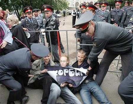 Police officers arrest human rights activists during a rally in central Moscow September 3, 2006. REUTERS/Alexander Natruskin