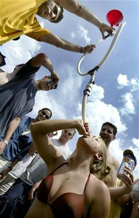 A college girl drinks beer through a funnel and pipe as thousands of college-age students gather on the infield in a traditional display of drunken fun on the day of the Preakness Stakes horse race at the Pimlico track in Baltimore, Maryland, May 15, 2004. REUTERS/Jason Reed