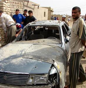 Residents gather near a damaged vehicle after clashes in Kut March 13, 2008. REUTERS/Jaafer Abed
