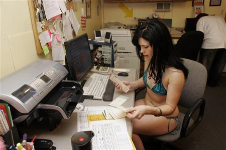 Lilah Mayhem reviews timecards in the office before her shift onstage, at the Lusty Lady peepshow in San Francisco, February 25, 2008. Work for the motley crew of dancers at San Francisco's Lusty Lady theater doesn't end when they step offstage, in an unprecedented move, the strippers decided to buy the peepshow from the owners and turn it into a worker-run cooperative. REUTERS/Erin Siegal