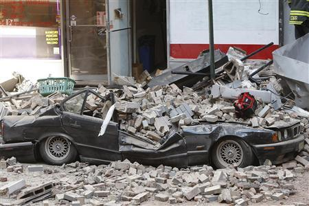 A rubble-covered car is seen near the site where a construction crane collapsed over a residential building in New York March 15, 2008. REUTERS/Chip East