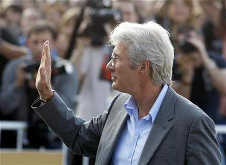 Richard Gere waves to photographers during a photo shoot at the San Sebastian International Film Festival, September 23, 2007. China should suffer a boycott of its cherished Beijing Olympics if it mishandles protests in restive Tibet, The Hollywood actor and Tibetan activist said on Friday. REUTERS/Vincent West