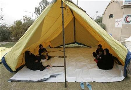 Shi'ite refugees sit inside a tent at a refugee camp in Baghdad's Sadr City December 5, 2007. REUTERS/Kareem Raheem