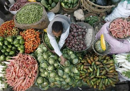 A vendor arranges vegetables at a wholesale market in the northeastern Indian city of Siliguri February 28, 2008. A gluten-free vegan diet full of nuts, sunflower seeds, fruit and vegetables appears to offer protection against heart attacks and strokes for people with rheumatoid arthritis, Swedish researchers said on Tuesday. REUTERS/Rupak De Chowdhuri