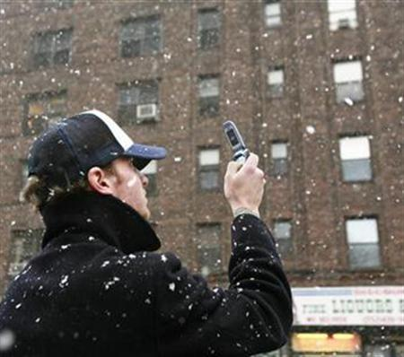 A pedestrian stops to take a photo of falling snow in New York, March 5, 2007. Google has seen an acceleration of Internet activity among mobile phone users in recent months since the company has introduced faster Web services on selected phone models, fueling confidence the mobile Internet era is at hand, the company said on Tuesday. REUTERS/Lucas Jackson