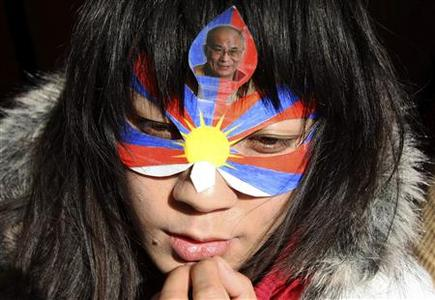 A Tibetan protester on hunger strike wears a mask with a picture of Tibetan spiritual leader Dalai Lama, as she sits in a tent in front of the Chinese embassy in Brussels to protest against China's crackdown in Tibet March 19, 2008. REUTERS/Francois Lenoir