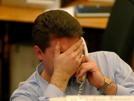A man covers his face at his desk in an undated file photo. Punishing a lazy team member can be counterproductive and it may be better to simply walk away, researchers said on Wednesday. REUTERS/Sergei Karpukhin