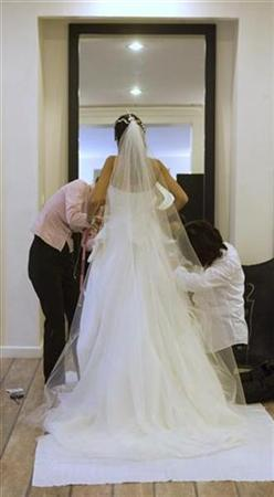 A woman tries on a wedding dress in a file photo. Marriage really can be a matter of the heart with a U.S. study finding that happily married couples have lower blood pressure than single people. REUTERS/Caren Firouz