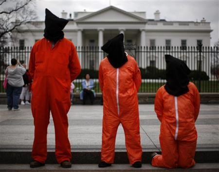 Protestors dressed as Guantanamo Bay prisoners stand in front of the White House during a demonstration marking the fifth anniversary of the U.S.-led invasion of Iraq, March 19, 2008. REUTERS/Jim Young