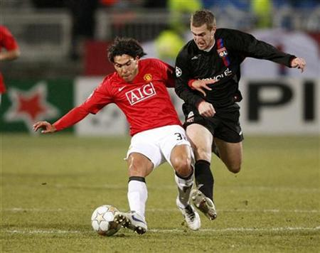 Manchester's United Carlos Tevez (L) challenges Olympique Lyon's Kim Kallstrom during their Champions League first knockout round, first leg soccer match at Gerland stadium in Lyon February 20,2008. REUTERS/Robert Pratta