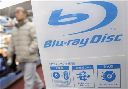 A shopper walks past a Blu-ray Disc logo at a store in Tokyo, February 18, 2008. The U.S. International Trade Commission said it would launch an investigation into some 30 companies including Sony Corp <6758.T> on possible patent infringements related to Blu-ray disc players and other products. REUTERS/Issei Kato