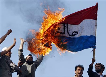 Afghans burn a Netherlands flag during a protest in Kabul March 21, 2008. Some 5,000 Afghans chanted ''death to Denmark and ''death to the Netherlands'' in the capital Kabul on Friday, protesting the reprinting of a cartoon of the Prophet Mohammad in Danish newspapers and a Dutch film on the Koran. REUTERS/Ahmad Masood