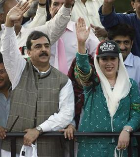 Yousaf Raza Gilani (L) and his party leader Benazir Bhutto wave to supporters upon her arrival in Karachi in this October 18, 2007 file photo. Pakistani President Pervez Musharraf assured full support to the incoming government on Sunday, a day after the party of slain former prime minister Benazir Bhutto nominated the country's next prime minister. REUTERS/Zahid Hussein/Files