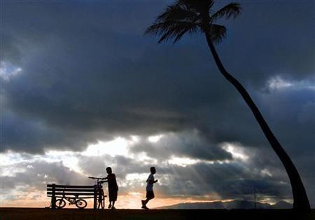 Two young boys end the weekend with their family during the sunset hours on Magic Island in Ala Moana Park in Honolulu, July 20, 2003. REUTERS/Lucy Pemoni