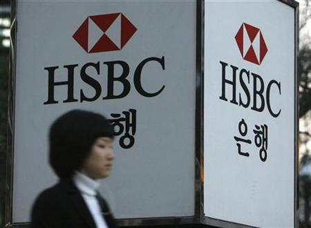 A woman walks past a HSBC logo at a branch office in Seoul March 5, 2008. HSBC has dropped out of the race to buy Singapore state investor Temasek Holdings' 42 percent stake in Bank Internasional Indonesia (BII) while South Korea's Kookmin has been shortlisted, a source briefed on the deal told Reuters on Tuesday. REUTERS/Jo Yong-Hak