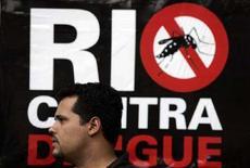 <p>Un passante a Rio de Janeiro davanti a un poster di sensibilizzazione sull'emergenza febbre dengue nello stato brasiliano. REUTERS/Bruno Domingos (BRAZIL)</p>