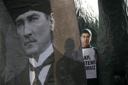 In this file photo a protester holds a sign as he stands behind a portrait of Mustafa Kemal Ataturk, founder of secular and modern Turkey, during a rally to support the ban on headscarves and to protest against the government in Ankara February 9, 2008. The Turkish government has been blocking access nationwide to Slide Inc and its popular multimedia Web software after a local court ruled the site let users post photos and stories insulting the Turkish republic's founder, the company said on Monday. REUTERS/Umit Bektas