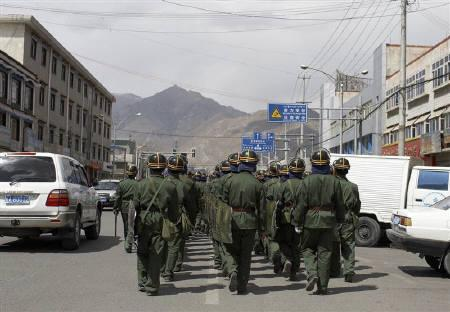Chinese riot policemen patrol the streets in Lhasa, Tibet March 25, 2008. At least two people have died in fresh protests in a Tibetan part of western China, reports said on Tuesday, as authorities made arrests in Tibet's capital Lhasa in an effort to reassert control over the restive region. REUTERS/Stringer