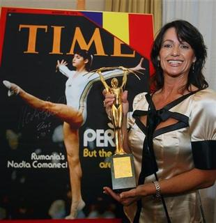 In this file photo Romanian Olympic gold medal gymnast Nadia Comaneci holds the ''Legendary Champions'' trophy, that was awarded by the Romanian presidency, as she stands in front of the August 1976 Time magazine cover in Bucharest September 15, 2006. REUTERS/Bogdan Cristel
