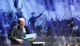 <p>Un esperto riordina gli spartiti dell'opera francese Les Miserables sullo sfondo di una scena della rivoluzione della fine del '700 in una foto d'archivio. REUTERS/Toby Melville</p>