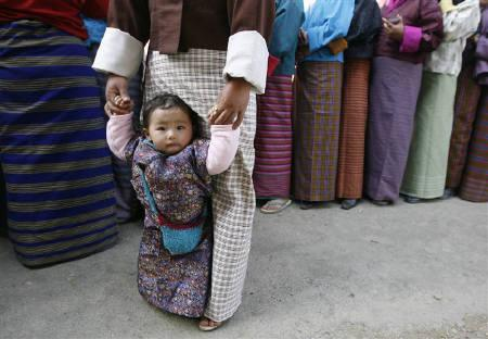 Bhutanese voters stand in a queue to cast their ballot outside a polling station in Thimpu March 24, 2008. After a century of absolute royal rule, when politics moved at a glacial pace, the Himalayan kingdom of Bhutan became the world's newest democracy this week. REUTERS/Desmond Boylan