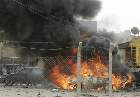 Vehicles burn after a U.S. air strike in a parking lot in Baghdad's Sadr City March 28, 2008. REUTERS/Kareem Raheem