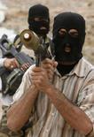<p>Вооруженные сторонники духовного лидера шиитов Ирака Моктады аль-Садра на улице Басры, 28 марта 2008 года. Духовный лидер иракских шиитов Моктада аль-Садр в воскресенье призвал своих вооруженных сторонников покинуть улицы Басры и других городов на юге страны, где они вели бои с правительственными войсками. (REUTERS/Atef Hassan)</p>