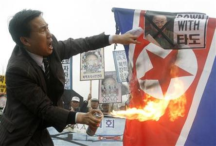 A protester burns a North Korean flag and a portrait of North Korea's leader Kim Jong-il during a rally in Seoul March 29, 2008. South Korea's military said on Saturday there were no signs North Korea would again test-fire missiles, a day after it launched a barrage of short-range rockets and threatened to attack the South Korean Navy. REUTERS/Jo Yong-Hak