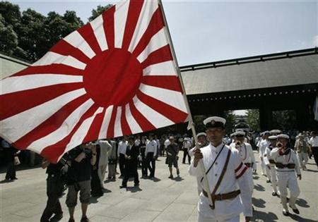 Men dressed in Japanese imperial naval uniforms march with imperial Naval ensigns, also known as the Rising Sun, at the Yasukuni Shrine, which honours wartime leaders convicted by an Allied tribunal as war criminals, along with millions of war dead, on the 62nd anniversary of Japan's surrender in World War Two, in Tokyo August 15, 2007. REUTERS/Kim Kyung-Hoon