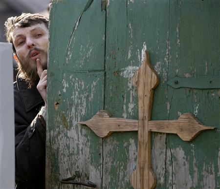 Pyotr Kuznetsov, the leader of a Russian doomsday cult, peeks out from behind the door of his house in the settlement of Nikolskoye in the Penza region March 31, 2008. REUTERS/Denis Sinyakov