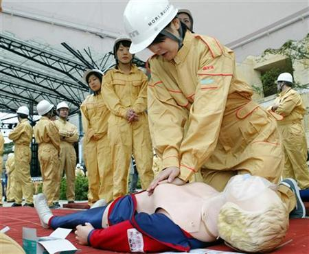 A female Japanese employee does the CPR (cardiopulmonary resuscitation) during a disaster prevention drill outside the Tokyo's Roppongi Hills complex in this file photo from September 1, 2003. REUTERS/Issei Kato