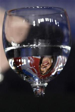 Sally Hawkins is reflected in a glass of water during a news conference in Berlin February 12, 2008. The notion that guzzling glasses of water to flood yourself with good health is all wet, researchers said on Wednesday. REUTERS/Tobias Schwarz